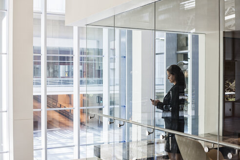 Businesswoman standing in a conference room window in a large business centre. - MINF08241