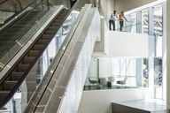 Businessman and woman at the top of an escalator in a large business centre. - MINF08247