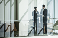 Businessman and woman standing behind a conference room window in large business centre. - MINF08250