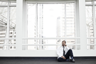 Black man doctor stressed out and sitting on floor. - MINF08271