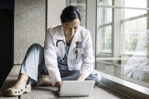 Asian woman doctor working on a lap top in a hospital  hallway. - MINF08274