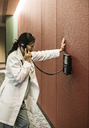 Asians woman doctor on a phone in a hospital lobby. - MINF08277