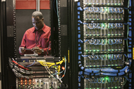 Black man technician working on computer servers in server farm. - MINF08283