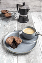 Chocolate muffin with liquid chocolate on plate with coffee cup - SARF03895