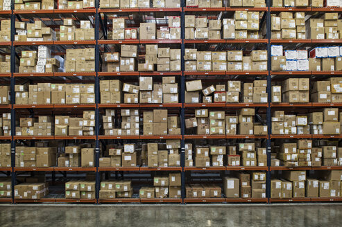 View of racks of cardboard boxes containing product in a large distribution warehouse. - MINF08388