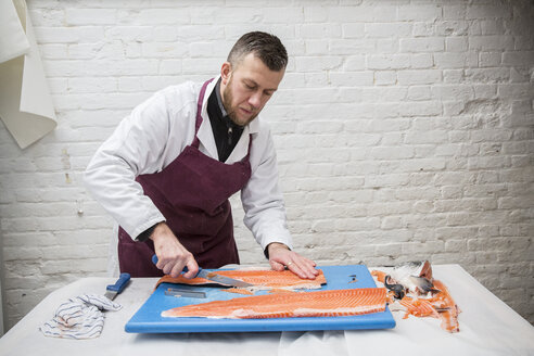 Man wearing apron standing at a table, cutting and filleting fresh salmon on blue chopping board. - MINF08433