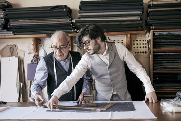 A tailor and a younger man, an assistant or apprentice working together, measuring cloth and cutting patterns. - MINF08490