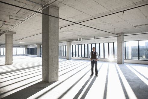 Asian businessman standing in a large empty raw office space. - MINF08543