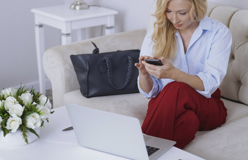Blond woman sitting on couch, using laptop and smartphone - AZF00069