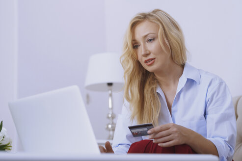 Blond woman sitting on couch, using laptop to make a payment with her credit card - AZF00072