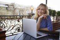 Female blogger working in coffee shop, using laptop - AZF00075