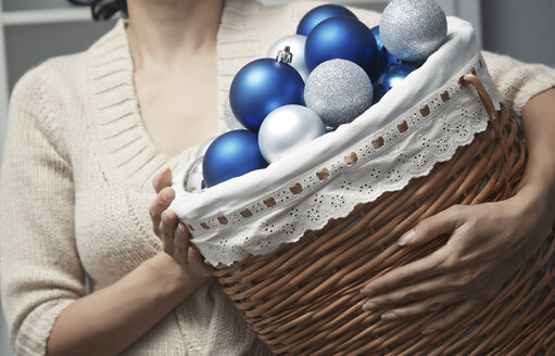 Woman carrying basket full of Christmas baubles - AZF00084
