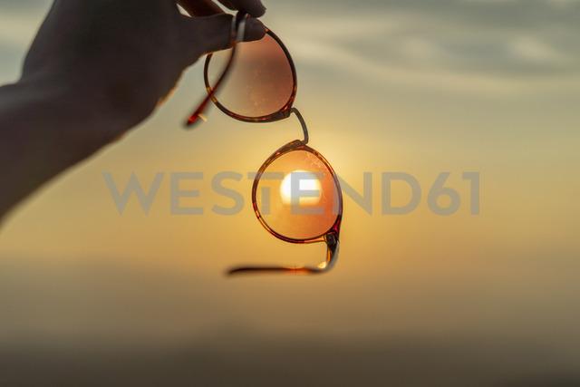Hand holding sunglasses against sunset - AFVF01380