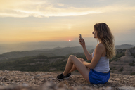 Spain, Catalonia, Sant Llorenc del Munt i l'Obac, woman taking pictures in the mountains with her smartphone - AFVF01386
