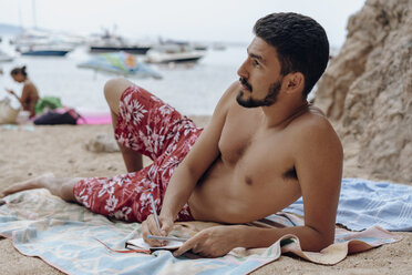 Young man lying on towel at the beach, notebook, thoughtful - AFVF01389
