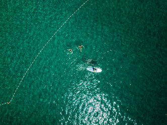 Croatia, Cres, Adriatic Sea, Aerial view of stand up paddle surfing and swimmers - DAWF00704