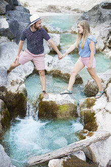 Young couple crossing river - MAEF12692