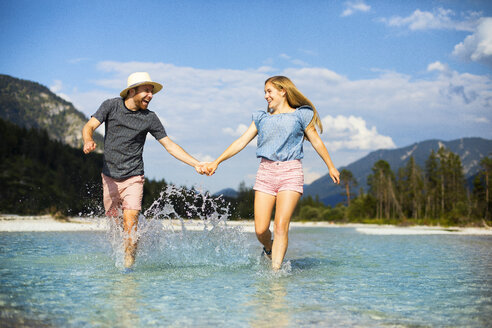 Young couple holding hands and running through water - MAEF12704