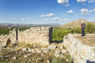 Greece, Peloponnese, Argolis, Tiryns, archaeological site, Cyclopean masonry. castle wall, Tourist looking at view - MAMF00193