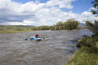 A man rafts down a river on a beautiful day in Montana. - AURF00256