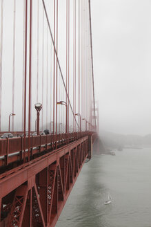 A small sailboat passes under the Golden Gate Bridge on a foggy day in San Francisco, California. - AURF00391