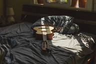 Acoustic guitaron top of a bed with sunlight coming through the window - AFVF01396