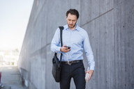 Businessman with earbuds walking along concrete wall looking at smartphone - DIGF04806