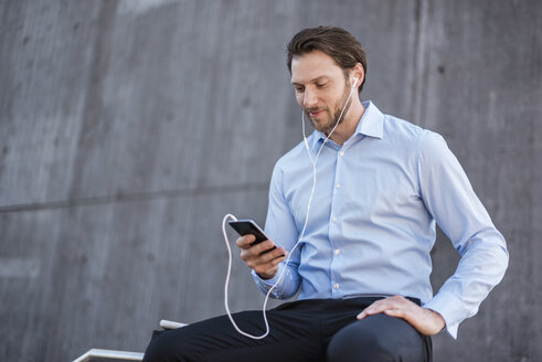 Businessman with earbuds sitting on a railing looking at smartphone - DIGF04809
