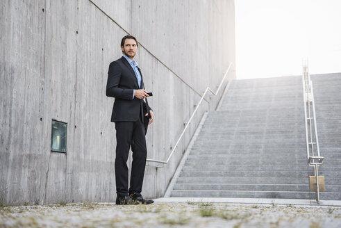 Businessman standing at stairs holding smartphone - DIGF04824