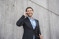 Smiling businessman at concrete wall talking on smartphone - DIGF04827