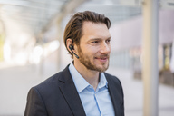 Portrait of smiling businessman wearing headset outdoors - DIGF04833