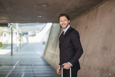Smiling businessman with rolling suitcase standing in underpass - DIGF04839