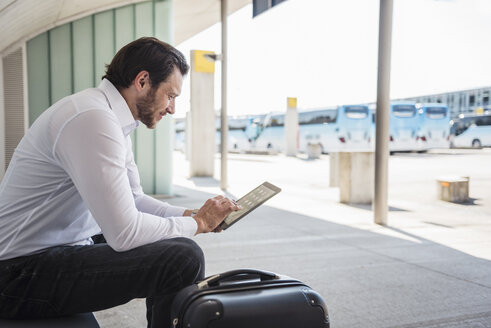 Smiling businessman with suitcase sitting at bus terminal using tablet - DIGF04848