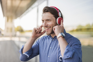 Portrait of happy man listening to music with headphones - DIGF04872