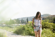 Smiling young woman walking on a rural path in summer - GIOF04138