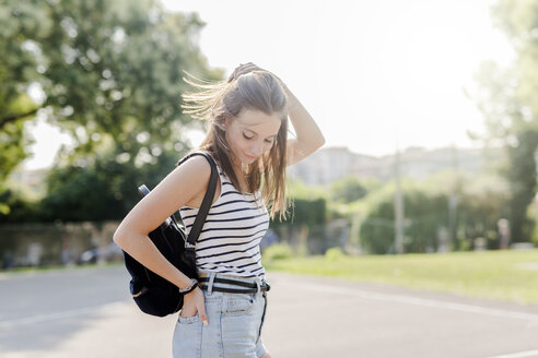 Portrait of smiling young woman with backpack outdoors in summer - GIOF04144