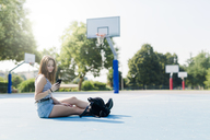 Young woman with backpack sitting on sports ground using cell phone - GIOF04147