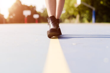 Legs of a woman wearing ankle boots walking on a line  on sports ground - GIOF04150