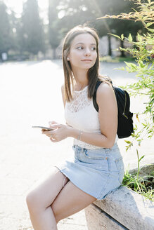 Young woman with backpack and cell phone resting in a park - GIOF04162