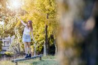 Young woman balancing on wood - GIOF04165