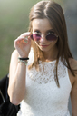 Portrait of young woman wearing sunglasses outdoors - GIOF04174