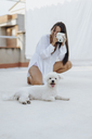 Portrait of white dog lying on roof terrace while young woman in the background taking photo - AFVF01410