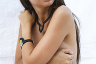 Young woman wearing modern bracelet and necklace, partial view - AFVF01422