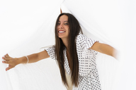 Portrait of young woman having fun with drying bed sheets on roof terrace - AFVF01425
