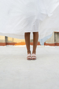 Legs of young woman hiding behind drying bed sheet - AFVF01428