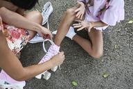 Mum tying pink roller skates at daughter - IGGF00507