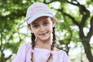 Portrait of little girl with green eyes braids and cap, smiling - IGGF00510
