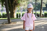 Portrait of smiling little girl with braids and cap - IGGF00513