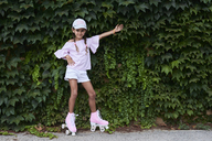 Cheerful little girl posing against ivy plants with pink roller skates in a park - IGGF00516