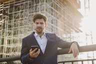 Businessman standing on bridge in front of construction site using cell phone - DIGF04880